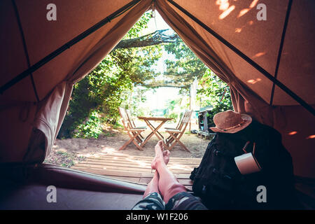 view of crossed legs of a hiker man resting barefoot in a camping tent, travel discovery concept, point of view shot - Stock Image
