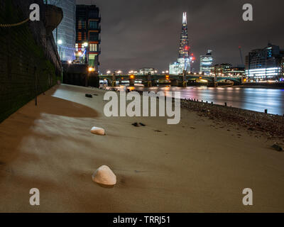 London, England, UK - March 7, 2019: Rocks are left on the sandy shore of the River Thames at low tide in central London, with Southwark Bridge and Th - Stock Image