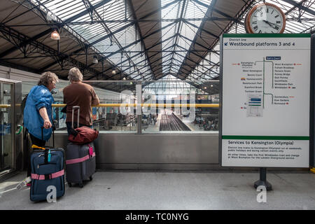 A couple of people with suitcases and a map detailing possible routes at Earl's Court London Underground Station, London, UK - Stock Image