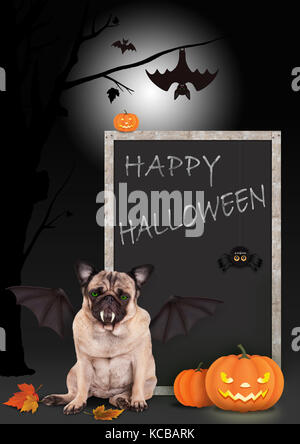 pug dog dressed up as bat, with pumpkins and blackboard sign with text happy halloween, on scary background - Stock Image