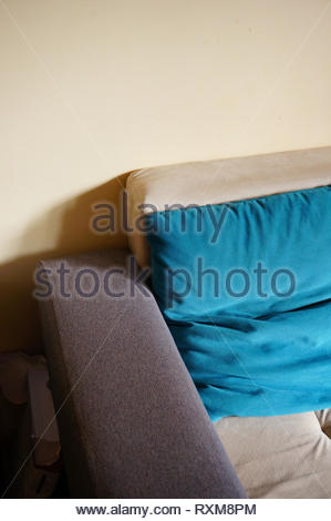 Close up of a comfortable sofa with blue pillow in a room. - Stock Image