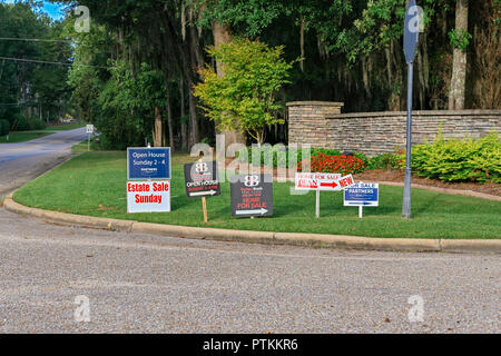 Row of real estate for sale signs along the road leading into a suburban residential neighborhood in Montgomery Alabama, USA. - Stock Image