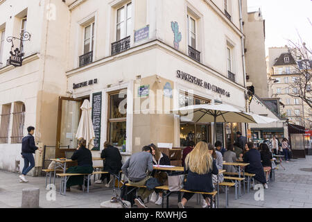 People chatting at Shakespeare and Company Café in Paris, France. - Stock Image