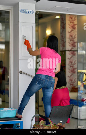 Woman DIY. Female painting shop front - Stock Image