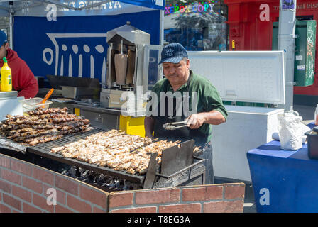 A local man selling greek brochette at a stand, Weekend market, woodside, queens, Queens, New York, , ny, united states of america, usa - Stock Image
