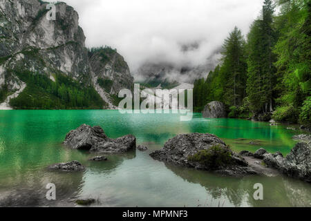 Lake of Braies in a cloudy summer day with forest around and fog in the background, Dolomites - Italy - Stock Image