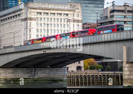 NOVEMBER 13, 2018, London, United Kingdom : Iconic new red London double decker passenger buses over the Thames in London Bridge. - Stock Image