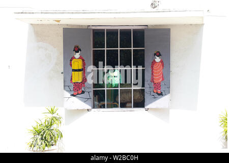 A Chinese cafe window with Chinese ladies artwork made on the window gate. - Stock Image