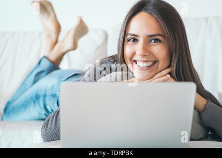 Young woman lying on sofa and using laptop at home - Happy girl surfing online with her computer while smiling at camera - Stock Image