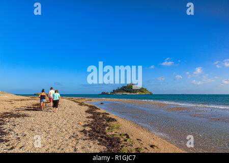 14 June 2018: Marazion, Cornwall, UK - Group of people walking on the beach and St Michaels's Mount. - Stock Image