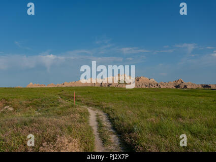 Trail Through Field Below Badlands Rock Formations - Stock Image