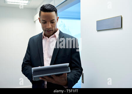 Businessman using digital tablet in hotel lobby - Stock Image