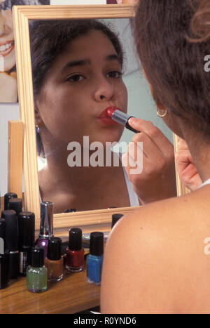 child putting on lipstick in mirror - Stock Image