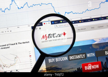 MONTREAL, CANADA - APRIL 26, 2019: MyBTC.ca cryptocurrency digital assets exchange logo and home page on a laptop screen under magnifying glass. - Stock Image