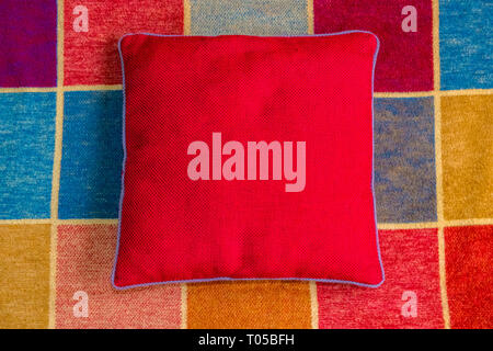 Red covered cushion on a multi coloured squared rug. - Stock Image