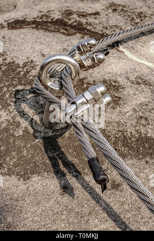 Climbing anchor or carabiner attached to the cliff rock. Difficult path for  climbing on via ferrata - Stock Image