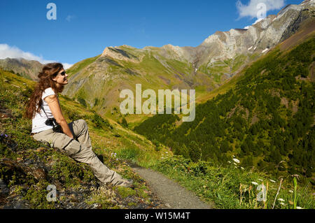 Female hiker resting in Transpirenaica GR-11 footpath with Posets massif at the back (Viadós, Chistau valley, Sobrarbe, Huesca, Pyrenees,Aragon,Spain) - Stock Image