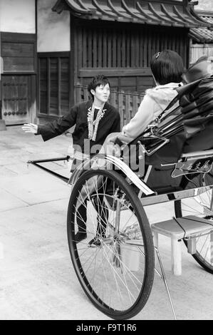 A male tour guide and rickshaw driver at the Sensō-ji temple (金龍山浅草寺) in Asakusa, Tokyo, showing a temple gate to - Stock Image