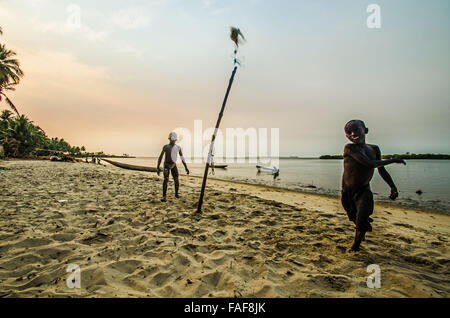 Boys playing at sunset on a beach in Sierra Leone's Turtle Islands. - Stock Image
