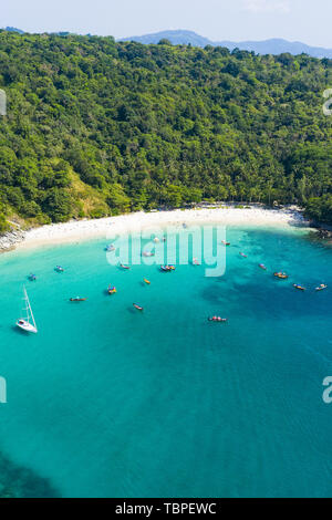 View from above, stunning aerial view of a beautiful tropical beach with white sand and turquoise clear water, long tail boats and people sunbathing. - Stock Image