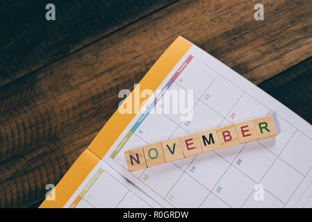 closeup of NOVEMBER alphabet tile on planner book calendar on wooden table . Planning and November month concept - Stock Image