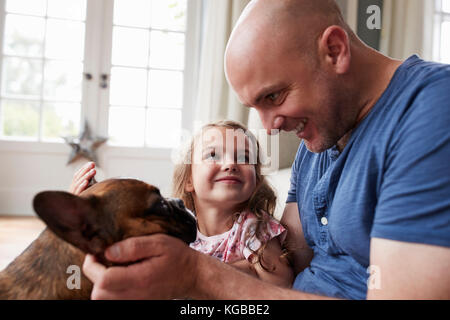 Young girl with her father petting dog at home, close up - Stock Image