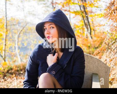 Beautiful teenager girl wearing hooded jacket serious looking at camera suspicious - Stock Image