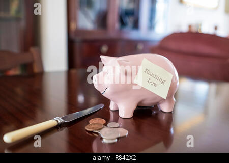 Pink piggy bank on wooden dining table with scattered coins and knife and a notelet with the text running low. - Stock Image