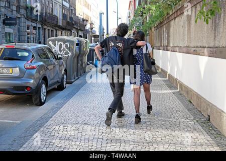 Young couple rear back view walk together along Rua de Cedofeita pavement sidewalk after work in spring Porto Portugal Europe EU  KATHY DEWITT - Stock Image