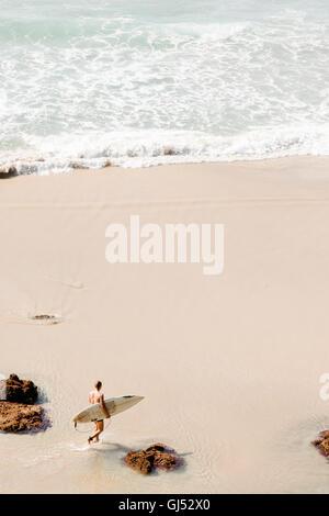 A man carrying a surfboard walking along Wategos Beach in Byron Bay. - Stock Image