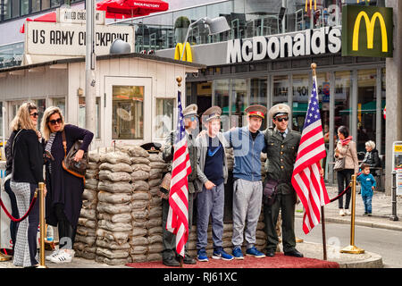 22 September 2018: Berlin, Germany - Tourists having photos taken at Checkpoint Charlie. - Stock Image