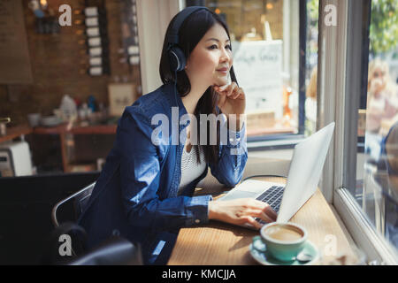 Pensive young woman listening to music with headphones at laptop and drinking coffee in cafe window - Stock Image