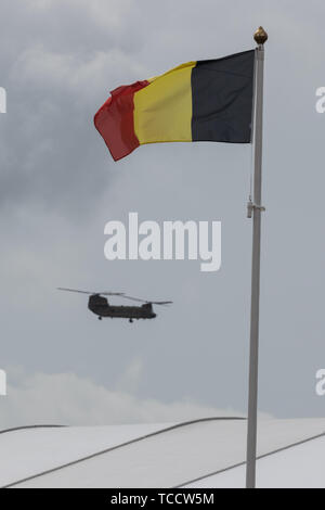 A chinnook helicopter flying past a Belgian flag on a flag pole - Stock Image