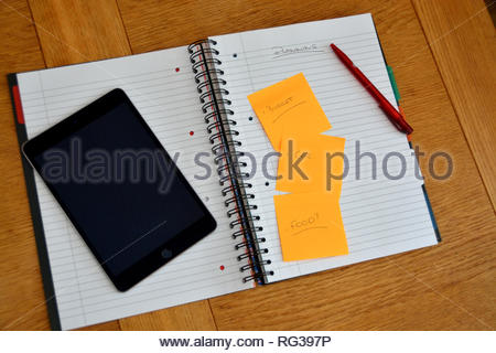 Planning, to do list, paper and red pen on a brown wooden table. Black tablet and sticky notes used for planning and organisation. Looking ahead and l - Stock Image