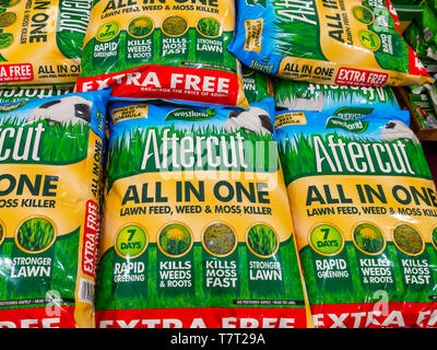 A stack of bags of Aftercut lawn feed weed and moss killer for sale  in a garden centre - Stock Image