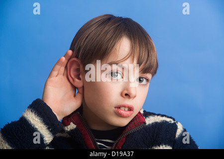 Boy aged 8 on a blue background cupping ear to improve hearing. Showing use of the sense to hear. - Stock Image