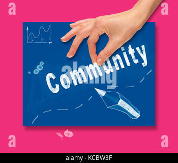 A hand picking up a Community concept on a colorful drawing board. - Stock Image