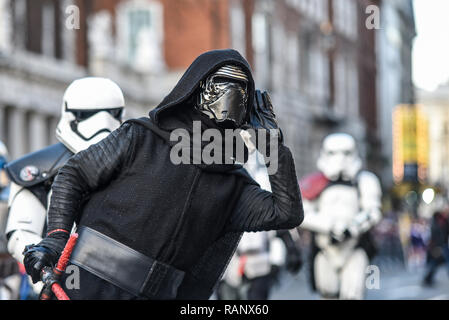 Kylo Ren costume of fictional character in the Star Wars films at London's New Year's Day Parade, UK. Listening, cupping ear, to boos from crowds - Stock Image