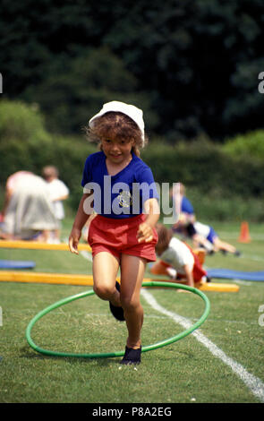 Little girl participating in obstacle race during primary school sports day - Stock Image