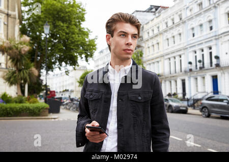 Young man standing in street holding smartphone looking away - Stock Image
