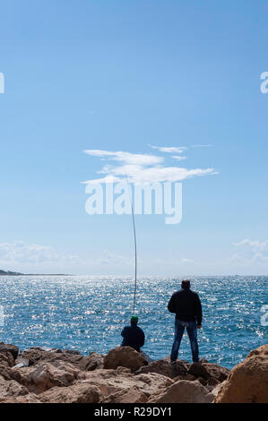 Men fishing in Paphos Harbour, Paphos (Pafos), Pafos District, Republic of Cyprus - Stock Image