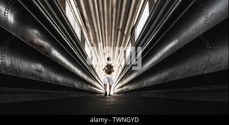 Lonely traveler man with backpack wolking in a steel urban tunnel - city tourism in rare scenic places concept - exploring outdoor and indoor - people - Stock Image
