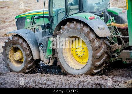 John Deere tractor operating in a muddy field. - Stock Image