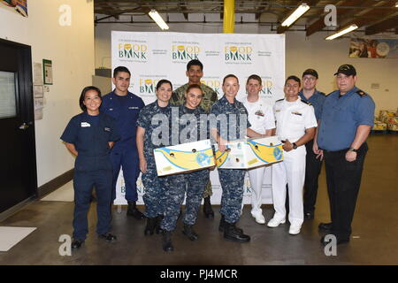 Service members from the U.S. Coast Guard, U.S. Navy, and Royal Canadian Navy stand in gratification after helping package enough food to provide over 6,000 meals for families in need at the Los Angeles Regional Food Bank, in Los Angeles, California, August 30, 2018. The LA Regional Food Bank since 1973, has worked to mobilize resources in the community to alleviate hunger. U.S. Coast Guard photo by Petty Officer 3rd Class DaVonte' Marrow. - Stock Image