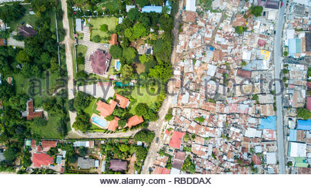Oyster Bay / Masasani, Dar es Salaam. AMAZING aerial images have captured the stark contrast and inequality where rich meets poor all across the world. The spectacular bird's eye view pictures show the landscape as an affluent area gives way onto one where people may be suffering from poverty. The stunning shots show this crossover of the rich and poor all across South Africa, Kenya, Mexico and even the USA. The remarkable photographs form of africanDRONE founder and photographer Johnny Miller's (37) Unequal Scenes project. Johnny Miller / mediadrumimages.com - Stock Image