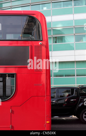 A red double decker bus passes a black car outside a green glass building in London - Stock Image