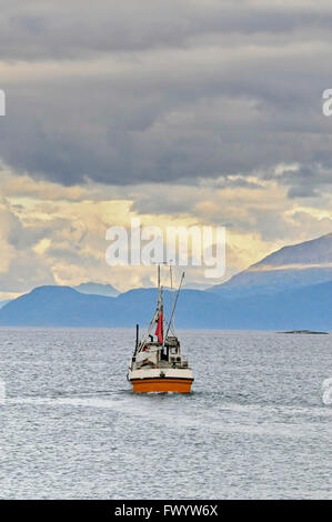 A fishing boat crossing a fjord near Harstad in northern Norway. - Stock Image