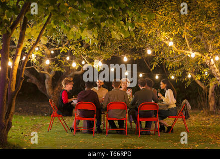 Friends enjoying dinner garden party under trees with fairy lights - Stock Image