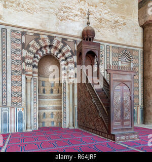Colorful decorated marble wall with engraved niche (Mihrab) and wooden platform (Minbar) at the Mosque of Al Nasir Mohammad Ibn Qalawun - Stock Image