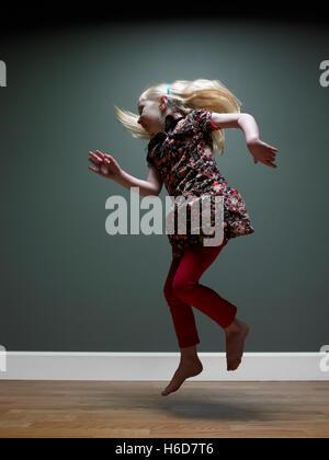 Girl jumping (3-5), studio shot - Stock Image